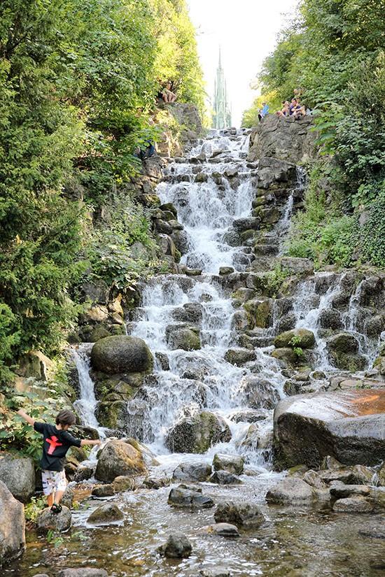 Een spelend kind voor de waterval in het Viktoriapark van Berlijn