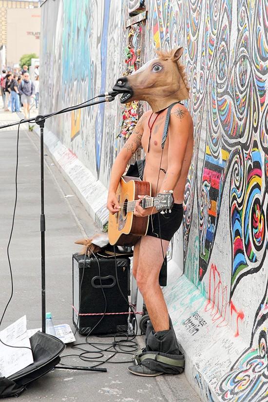 Naakte man met paardenmasker treedt op voor de East Side Gallery in Berlijn
